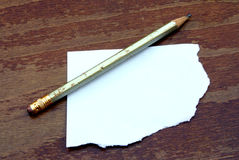 Pencil with paper. Pencil with scrap of paper on wooden table Royalty Free Stock Photos