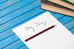 Pencil and paper with My Story words and books royalty free stock image