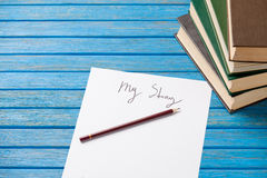 Pencil and paper with My Story words and books stock images