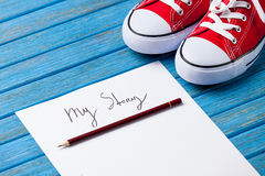Pencil and paper with My Story words near gumshoes. On blue wooden table Royalty Free Stock Photos