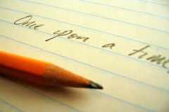 Pencil, paper, and opening line. Sharpened paper laying on lined paper beneath the words Once upon a time Stock Photography