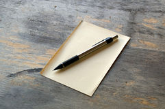 Pencil and paper on wood. A silver and black mechanical pencil on a sheet of yellow manila paper on a distressed wooden table Royalty Free Stock Photography