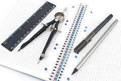 Pencil, pen, drawing compass, ruler on notebook Stock Photos