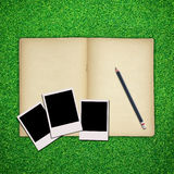 Pencil and photo frame with book on green grass Royalty Free Stock Photo