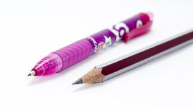 Pencil and a pink colored pen. Royalty Free Stock Images