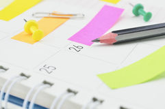 Pencil with post It notes and pin on business diary page Royalty Free Stock Images