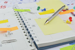 Pencil with post It notes and pin on business diary page Royalty Free Stock Image