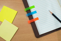 Pencil,post-it paper and notebook on wooden table. Top view Stock Photos