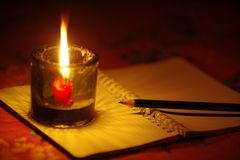 Pencil put on notebook with candle light. Royalty Free Stock Photo