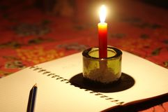 Pencil put on notebook with candle light. Royalty Free Stock Image