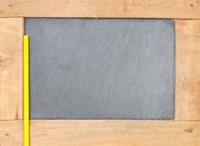 Pencil put on wooden slate board scene. Royalty Free Stock Images