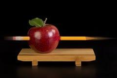 Pencil through red apple Stock Photos