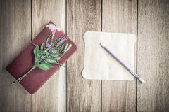 Pencil with red book on the old wooden background. Royalty Free Stock Photography