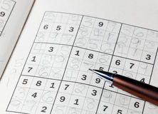 Pencil resting on sudoku book Royalty Free Stock Photos