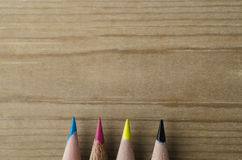 Pencil Row In CMYK Hues On Wooden Background Stock Images