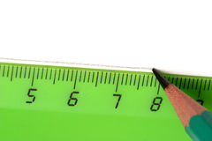 Pencil and ruler. Pencil drawing a line over a green ruler on the white paper Stock Photography