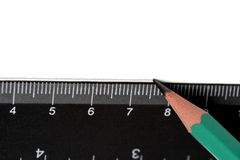 Pencil and ruler. Pencil drawing a line over a black ruler on the white paper Stock Photo