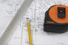 Pencil, scale, and tape measure on plans Stock Photo
