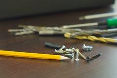 Pencil screws home repair. Pencil with metal screws engineering construction idea. Fix tool household. Home repair tools Royalty Free Stock Images