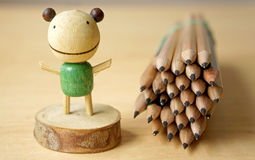 Pencil set with decorated wooden toy. On wooden table Stock Image