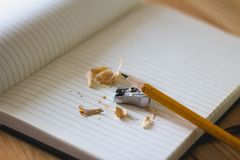 Pencil Sharpen Beside a Sharpener and Notebook Stock Photos