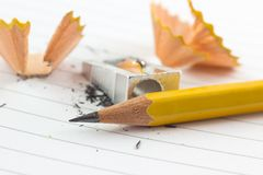 Pencil and sharpened. On a striped notebook sheet stock image