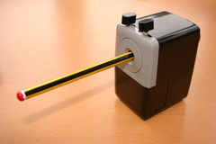 Pencil in a sharpener. Pencil sharpener sitting on a desk with a pencil already in it Stock Photography