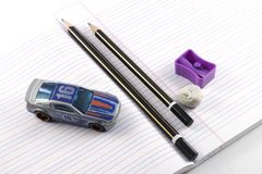 Pencil, Sharpener, Eraser, Book. Concept of work and play depicted using pencil, eraser, sharpener, book and a toy car Royalty Free Stock Images