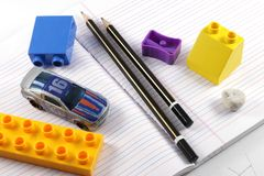 Pencil, Sharpener, Eraser, Book. Concept of work and play depicted using pencil, eraser, sharpener, book and a toy car and building blocks Royalty Free Stock Image