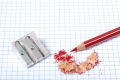 Pencil and sharpener rest on a square sheet with pencil shaving royalty free stock image