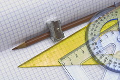 Pencil and sharpener with triangle. On workbook page Stock Photos