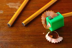 Pencil in a sharpener and two unsharpened pencils Stock Photography