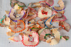 Pencil shavings. Colored pencil shavings on notebook sheet Stock Photos