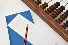 Pencil, sheet of paper and abacus Stock Photos