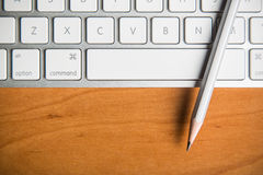 Pencil on silver metal keyboard Royalty Free Stock Photo