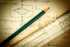 Pencil and a slide rule on old page with the calculations in Stock Photos