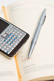 Pencil and smart phone on appointment book Stock Photos