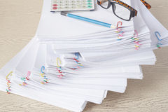 Pencil with spectacles and calculator on stack of overload paper royalty free stock photography