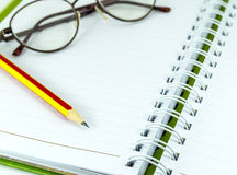 Pencil and spectacles on the datebook Stock Photos