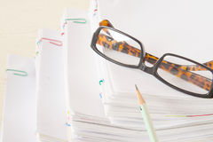 Pencil and spectacles put on stack of overload paper Stock Photos