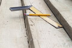 Pencil and a square line on the rafters. Construction of wooden houses and roofs.  stock image