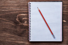 Pencil and squared notepad on pine brown wooden Stock Photos