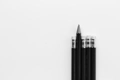 Pencil standing out from row of pencils. Stock Photos