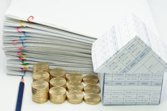 Pencil and step pile of gold coins with house. And pile overload document with colorful paperclip on white background Stock Photo
