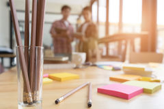 Pencil and sticky note on table with background of young univers Stock Image
