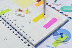 Pencil with sticky notes and pin on business diary page Royalty Free Stock Photography
