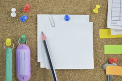 Pencil with sticky notes, pin, key and tag name on cork board Royalty Free Stock Photography