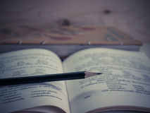 Pencil and  textbook. Placed on a wooden table (vintage Royalty Free Stock Photos
