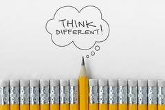 Pencil tip standing out from croud of pencil rubber erasers with Think different word on thought bubble royalty free stock photo