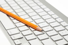 Pencil on top of a computer keyboard concept. Closeup concept of a lead pencil on top of a modern wireless computer keyboard Royalty Free Stock Photos